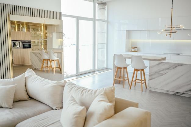 В скандинавском стиле светлая классическая современная роскошная гостиная-столовая и кухня с деревянными, белыми, мраморными деталями, новой стильной мебелью, уютным диваном-кроватью, минималистичным скандинавским дизайном интерьера.