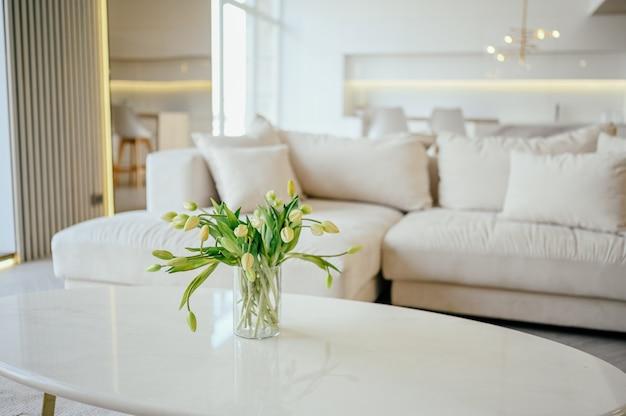 スカンジナビアスタイルの明るいクラシックモダンで豪華な白いリビングルーム。大理石のテーブル、新しいスタイリッシュな家具、チェスト、引き出し、心地よいアームチェア、ベージュのソファ、ソファ。最小限のノルディックインテリアデザイン