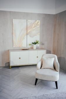 スカンジナビアスタイルの要素明るくクラシックでモダンで豪華なリビングルーム、木製、白、大理石のディテール、新しいスタイリッシュな家具、箪笥、居心地の良いアームチェア。最小限のノルディックインテリアデザイン