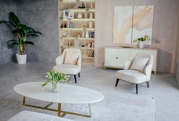 スカンジナビアスタイルの明るいクラシックモダンで豪華な白いリビングルーム。大理石のテーブル、新しいスタイリッシュな家具、箪笥、居心地の良いアームチェア、室内植物。最小限のノルディックインテリアデザイン