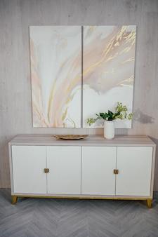 スカンジナビアスタイルの要素明るいクラシックモダンで豪華なリビングルーム、木製、白、大理石のディテール、新しいスタイリッシュな家具、チェスト。最小限のノルディックインテリアデザイン