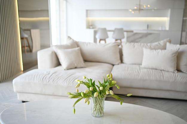 スカンジナビアスタイルの明るいクラシックモダンで豪華なリビングダイニングルームとキッチン、木製、白、大理石のディテール、新しいスタイリッシュな家具、居心地の良いソファーソファ、ミニマルな北欧のインテリアデザイン。