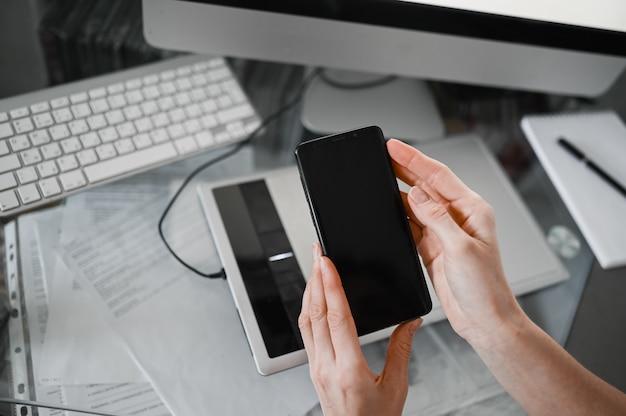 インテリア職場でスマートフォンを使用して女性の手、オフィスデスクで携帯電話を使用してフリーランスのビジネス女性、スマートフォンとノートブックコンピューターを使用して自宅から作業します。リモートワーカー検疫