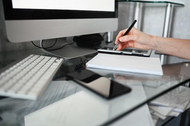 認識できない女性の手が空のノートブックとコンピューターに書き込みます。検疫中に自宅でスマートフォンとラップトップを使用するフリーランサー。インターネットマーケティング、金融、ビジネス、リモート作業の概念