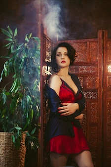 Фасонируйте портрет красивой молодой брюнетки в красном нижнем белье и черной рубашке в темном интерьере