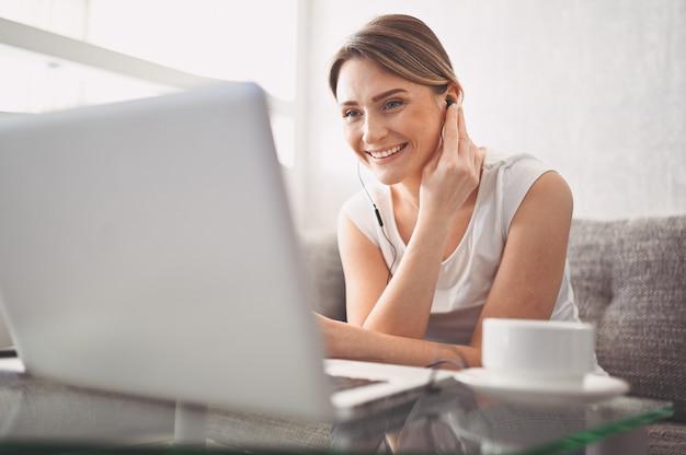 ラップトップコンピューター、ヘッドフォン、ビデオチャット、手を振って自宅でオンラインで勉強して魅力的な幸せな若い学生。リモートワーク、遠隔教育。検疫上のビデオ会議または仮想イベント