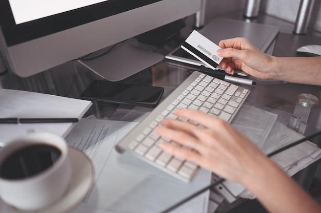 Непризнанная женщина держа кредитную карточку в руке и используя клавиатуру портативного компьютера. предприниматель или предприниматель работает. интернет-магазины, электронная коммерция, интернет-банкинг, концепция тратить деньги
