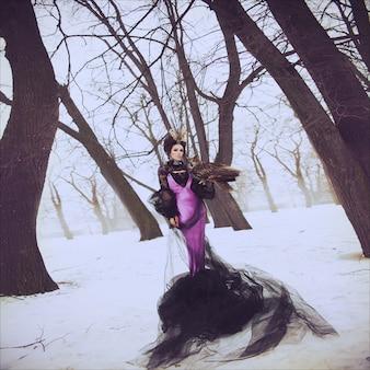 Фасонируйте портрет зимы красивой брюнетки в длинном платье сирени с сычом орла. креативная прическа и макияж. хэллоуин