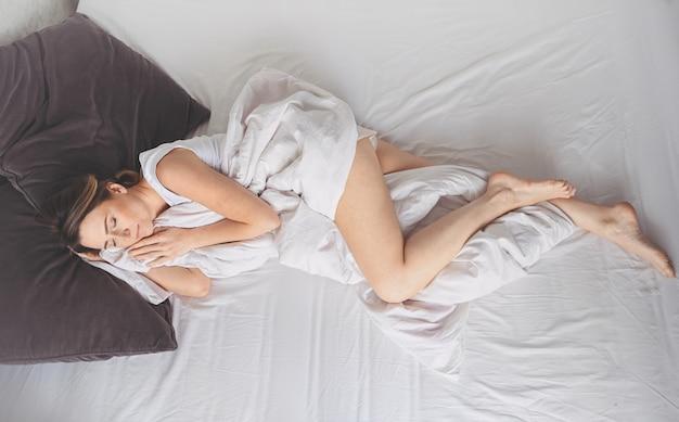 魅力的な笑顔の若い女性が一人で幸せな概念を目覚めさせるベッドでストレッチ、居心地の良い快適なベッドとマットレスで健康的な睡眠後に目を覚ますおはようを楽しむ