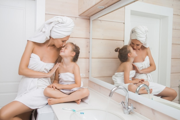 母と娘が浴室で抱き締めます。