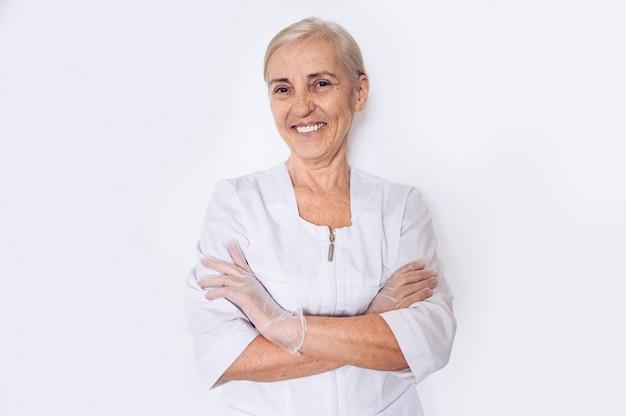 高齢者の笑顔の成熟した女性医師や看護師は白い背景で隔離の個人用保護具を身に着けている白い医療コート、手袋で腕を組んだ。ヘルスケアおよび医学の概念。