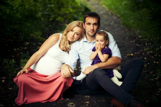 幸せな家族の夏の肖像画。妊娠中の母親、父親、小さな娘。