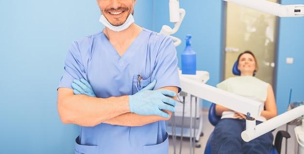 Доктор в синей медицинской форме в стоматологическом кабинете и пациент в стоматологическом кресле
