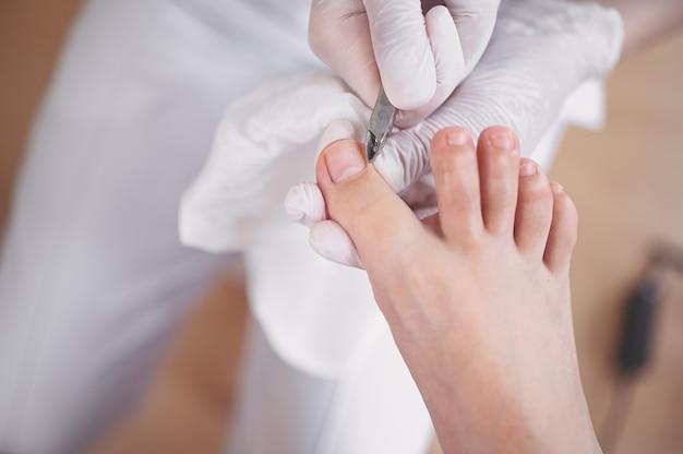 プロの医療ペディキュアの手順は、爪切りを使用してクローズアップ