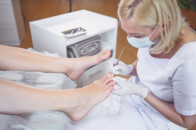 二重の爪の器具を使用してプロの医療ペディキュアの手順をクローズアップ