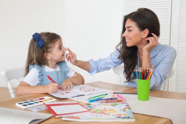 レッスンの準備をしている母と娘の笑顔と鉛筆と絵の具でテーブルに描く