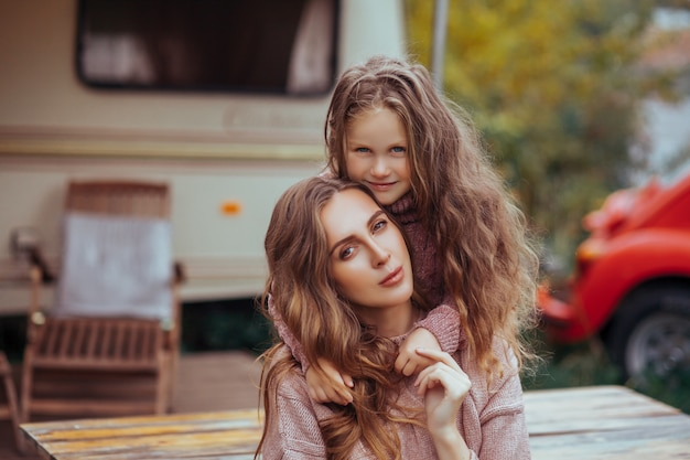 母と小さな娘の肖像画を抱き締めるとキャンピングカーの休暇に田舎でリラックス