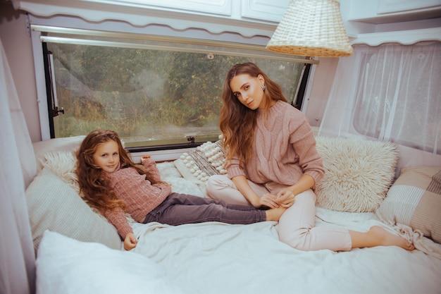 母と小さな娘リラックスしてキャンピングカーの中の田舎で楽しんで