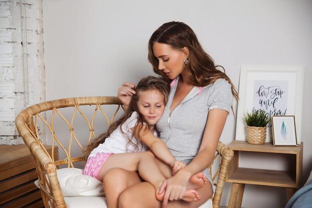 かわいい女の子と魅力的な若い女性は家で一緒に時間を過ごしています。幸せな家族の概念。ママと小さな子供がキスしてハグ