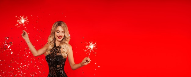 新年パーティーを祝う線香花火を持つ女性。紙吹雪を投げて光沢のある黒のドレスで美しい笑顔の少女の肖像画