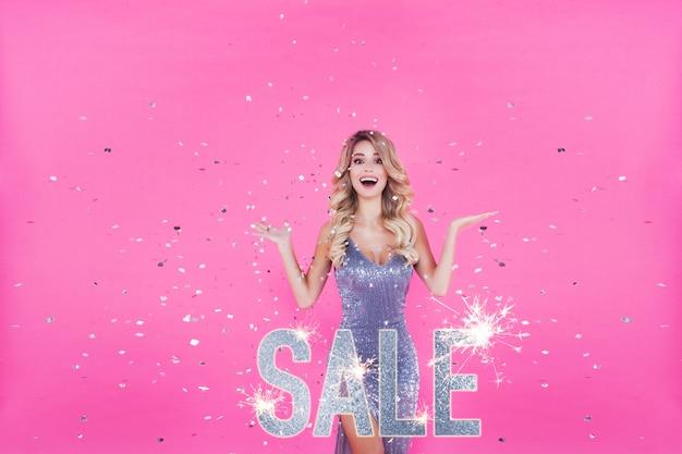 Фотография возбужденной милой блондинки, удивленной началом продаж на розовом