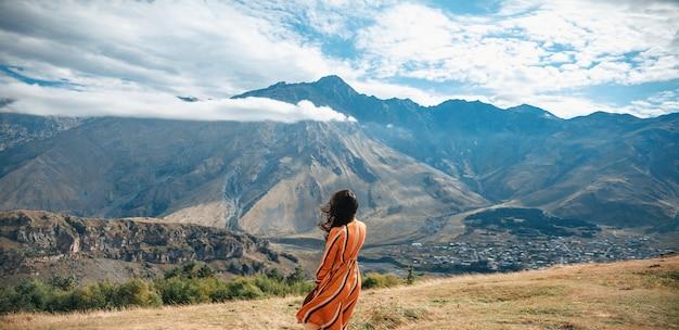 山と曇り空でポーズをとって屋外旅行ライフスタイル女性観光客。