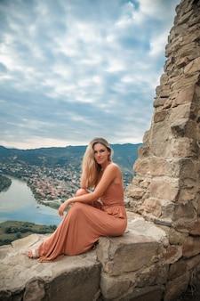 山と川を背景にポーズ女性を旅行します。