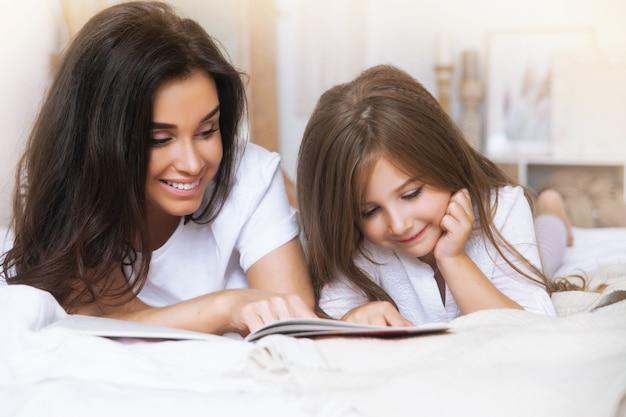 Портрет крупным планом улыбающейся матери и дочери, читающей в постели рано утром в белом скандинаве