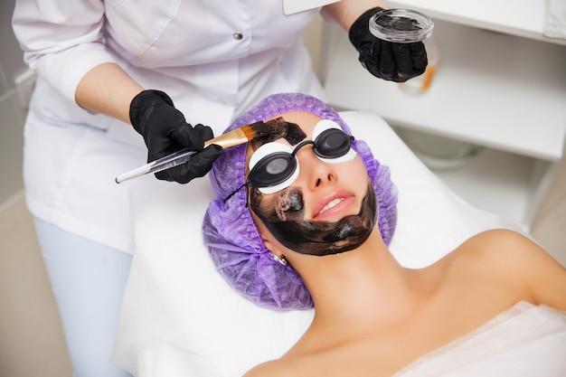 美容室でのカーボン面レーザー剥離手順のプロセス。レーザーパルスで顔の皮膚をきれいにします。ハードウェア美容治療。肌の若返り。彼女の顔にカーボンナノゲルを持つ若い女性