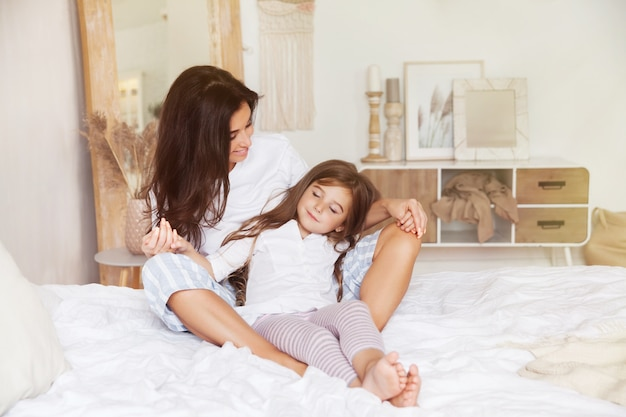 Маленькая дочь спит на руках у матери на кровати в скандинавском