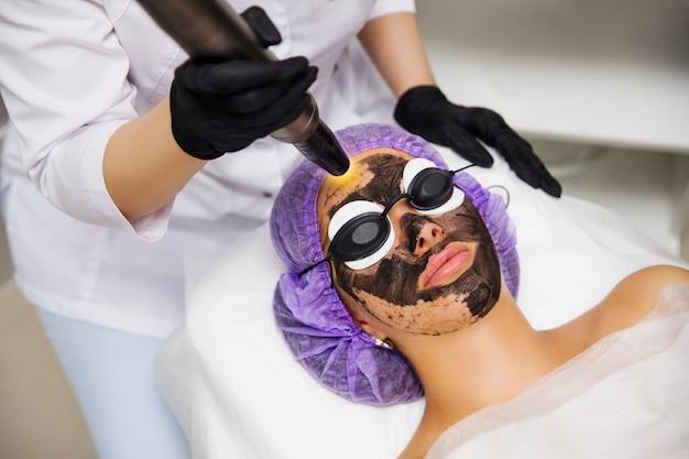 美容室でのカーボン面レーザー剥離手順のプロセス。レーザーパルスで顔の皮膚をきれいにします。ハードウェア美容治療。顔の肌の若返り、肌を温める