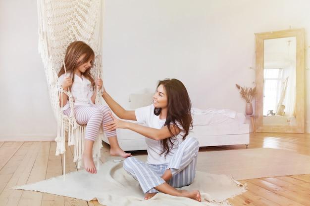 母はスカンジナビアの自宅でハンモックで小さな娘をスイングします。