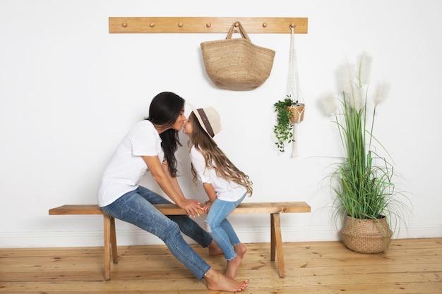 スカンジナビアのベンチに座っている麦わら帽子の小さな娘にキスの母
