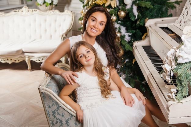 Счастливого рождества и счастливых праздников. веселая мама и ее милая дочь девушка в белом классическом интерьере белого пианино и украшенные елки. новый год