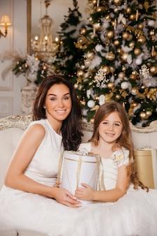 メリークリスマスとハッピーホリデー。陽気なお母さんと彼女のかわいい娘の女の子は白いクラシックインテリアピアノと飾られたクリスマスツリーでプレゼントを交換します。新年