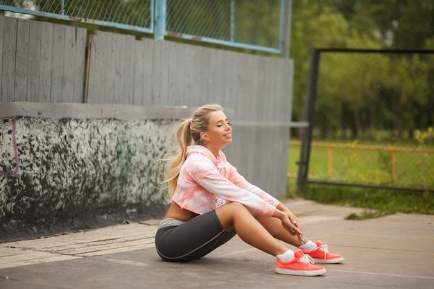 アスレチックフィールドでスポーツ演習を行うファッションスポーツウェアの美しい健康フィットネスブロンド女性。