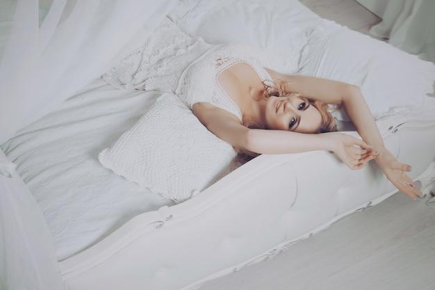 Фасонируйте фото искусства красивой чувственной молодой белокурой женщины в белом неглиже женское бельё с составом и прической в ее будуаре. домашняя спальня белого цвета. леди готовится ко сну