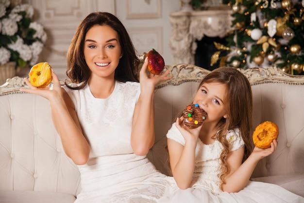 ドーナツを楽しんで美しい母と小さな女の子