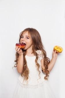 Возбужденная маленькая девочка позирует с пончиками