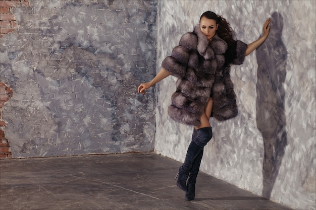Зимняя мода стиль. красивая женщина в роскошной шубе на голое тело с сапогами.