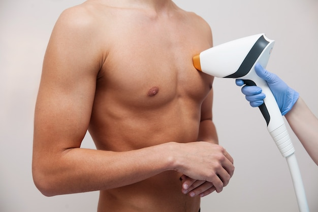 滑らかな澄んだ肌を持つ筋肉アスリート男。ビューティーサロンでの脱毛と脱毛。男性のレーザー脱毛のコンセプト。手順のための近代的な装置を使用して美容師。スキン&ビューティーケア