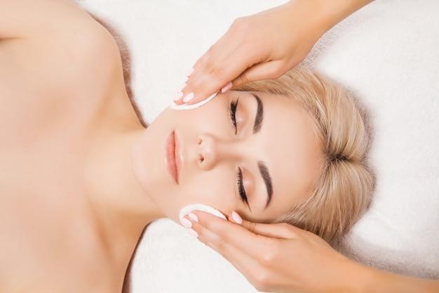 美容師は美容院でスポンジで肌の女性をきれいにします。完璧なクリーニング-スパトリートメントスキンケア顔。スキンケア、美容、スパのコンセプト