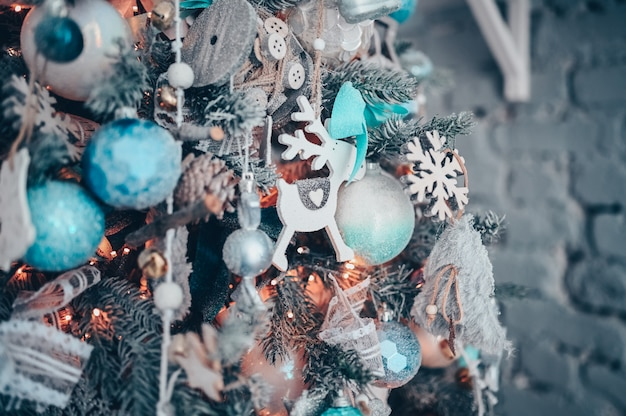白いおもちゃの鹿と暗いターコイズとオレンジ色のクリスマス装飾ツリーの詳細