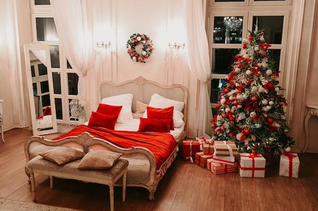 Новогодний классический интерьер спальни белого цвета с украшенной елкой в классических белых и красных тонах с подарочными коробками.