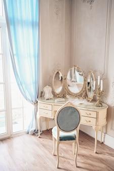 ブドワールドレッシン女性用の私室ドレッシングテーブルと白い寝室のインテリアの詳細。