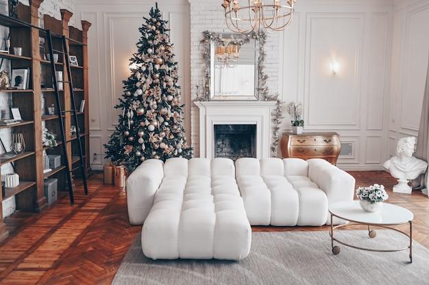 Современная гостиная белого интерьера с классическими элементами и украшенной елкой