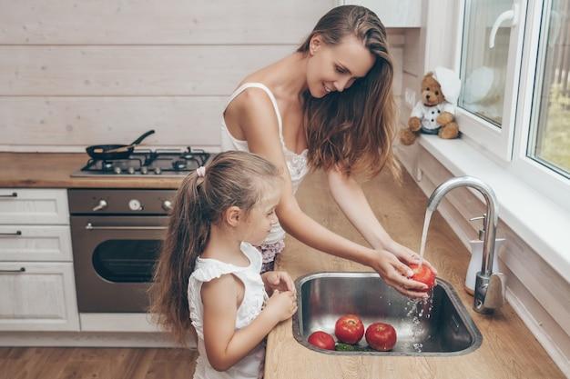 母と娘が調理し、台所で野菜を洗う
