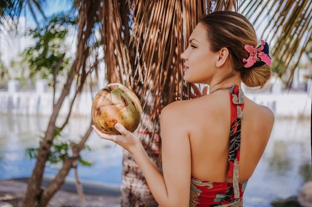 ジャングルの熱帯公園でポーズをとってココナッツを持つ旅行者金髪美人