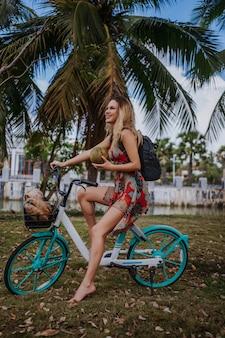 ジャングルの熱帯公園で自転車に乗ってココナッツを持つ旅行者金髪美女。