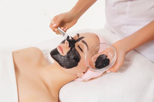 フェイスピーリングカーボンマスク、スパビューティトリートメント、スキンケア。スパサロンで美容師によって顔のケアを得る女性。美容クリニックで目を閉じてソファに横たわっているモデル。ヘルスケア美容